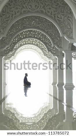 A highkey image of a Muslim prays.