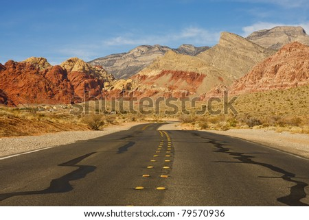 A highway curving through the desert into distant mountains