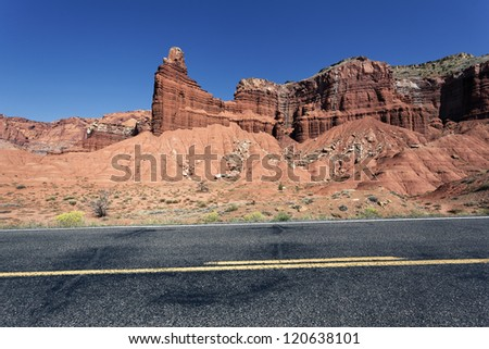 A highway rolling through red rock canyons