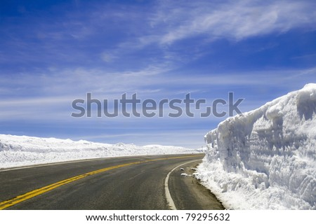 A highway that disappears around a corner is surrounded by snow walls that have been cut by a plow on a sunny day