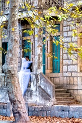 A hijabi weiled muslim woman getting married infront of a vintage house during the Fall season