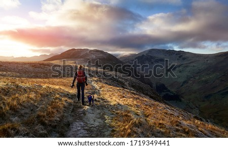 A hiker and their dog walking towards the mountain summit of High Spy from Maiden Moor at sunrise on the Derwent Fells in the Lake District, UK. Stock photo ©