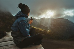 A hiker girl sits on the viewpoint and eats an energy bar, watching the sunset on the mountains