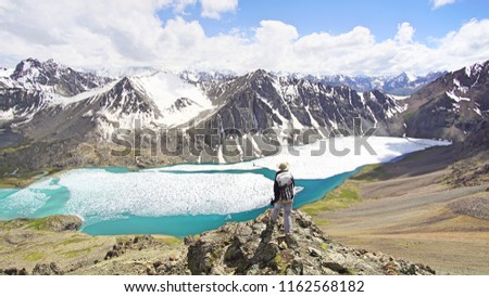 A hiker girl standing above Ala-Kul lake in the mountains of Kyrgyzstan.