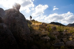 A hiker goes uphill on rocky steep ground, backlit under the clouds and blue sky