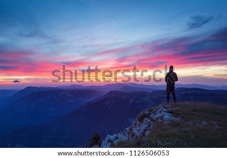 A hiker is looking at a tranquil, pink sunset in a mountainous wilderness.