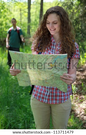 A hiker is reading a map for orientation.