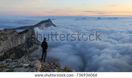 A hiker looking over a sea of clouds in the mountains at dawn.