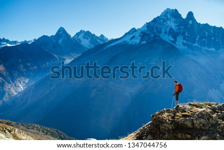 A hiker looking over the vast landscape of the mountains in the Alps while enjoying the view