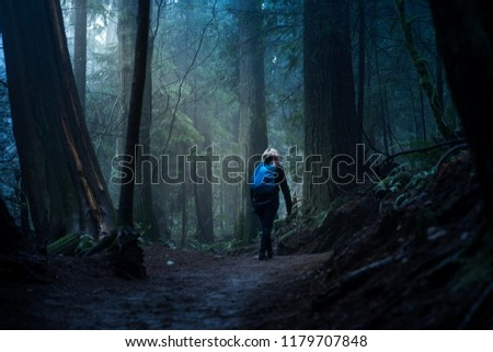 A hiker on an creepy moody path in the forest of British Columbia near Vancouver Canada