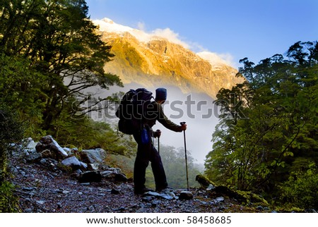 A hiker pauses for a rest at a clearing while ascending into the mountains