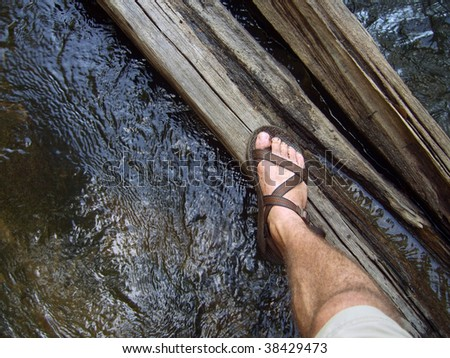 A hiker's view stepping across a log in a river