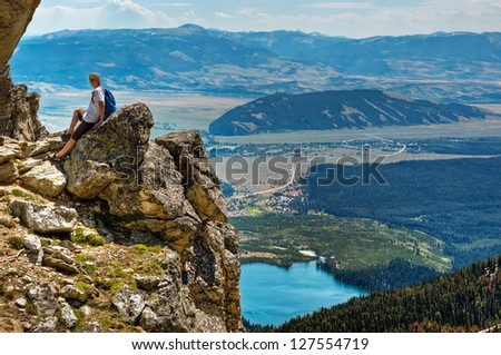 A hiker sits above the Grand Teton valley below at over 9700 feet near Amphitheatre Lake at the top of the Lupine Meadows trail, Grand Teton National Park, Wyoming.