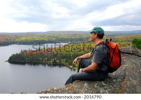 A hiker sitting on a cliff edge enjoying scenic view