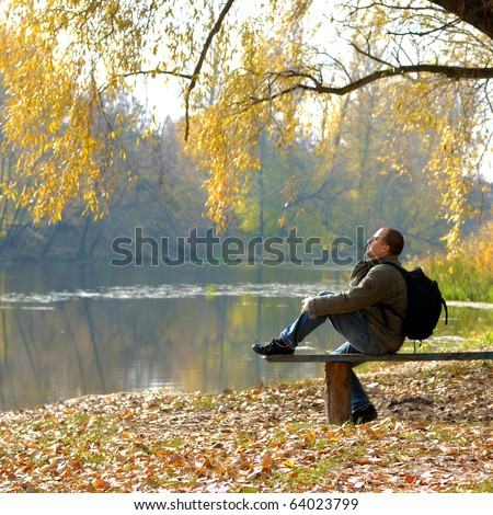 A hiker sitting on the bench near river