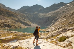 A hiker takes photos of the natural landscape with a reflex camera, in a lake with turquoise waters that reflect the mountains in summer, Aragonese Pyrenees, Huesca, Posets-Maladeta Natural Park.