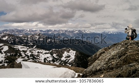 A hiker taking a photograph of the stunning view of snow capped mountains after climbing the ridge. (BC, Canada)