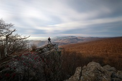 A hiker taking in the views of Shenandoah National Park from Mount Marshall on a Winter morning.