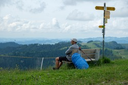 A hiker with a big backpack rests on a bench in the Bernese Oberland