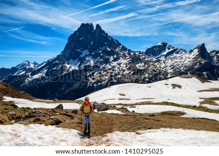 a hiker woman walking in the french Pyrenees mountains, Pic du midi d Ossau in background
