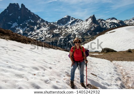a hiker woman walking in the snow, in french Pyrenees mountains, Pic du midi d Ossau in background