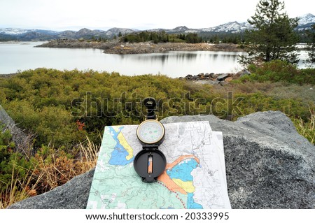 A hiking map and compass overlooking a lake in the California sierra Nevada mountains.