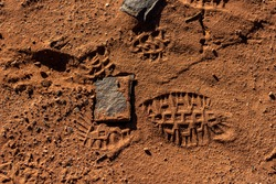 A hiking shoe footprint in a brown desert sand with a part of it on some square rock that looks misplaced.