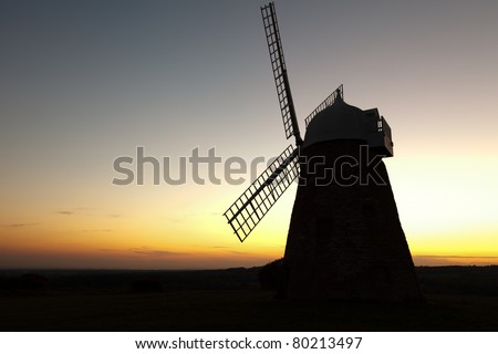 A hill top windmill silhouetted against the sky after sunset.