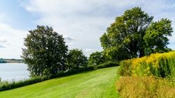 A hilltop garden with a view of Kolding Fjord. The trees stand tall and green and the flowers bloom beautifully.