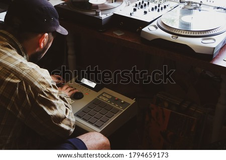 A hip hop composer, beatmaker creates beats on a digital production controller with pushbutton pads. The DJ plays the beats live on the pad controller of digital audio equipment. Rap music Foto d'archivio ©