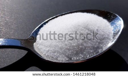 A hip of granulated sea salt in a spoon.