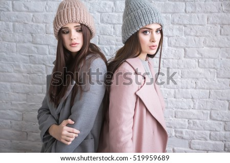 A hipster casual girls with long brown hair wearing a stylish coat and knit cap is looking aside while standing on a light white brick background on a street. Horizontal mock up.