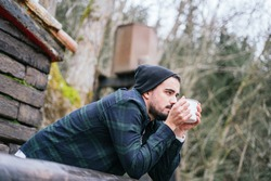 A hipster guy drinking coffee on the cottage terrace, melancholic autumn mood