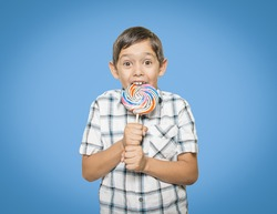 A Hispanic boy excitedly licks a very large lollipop. He is wearing a plaid shirt and is in front of a blue background.
