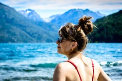 A Hispanic female in sunglasses posing in the scenic waterscape background