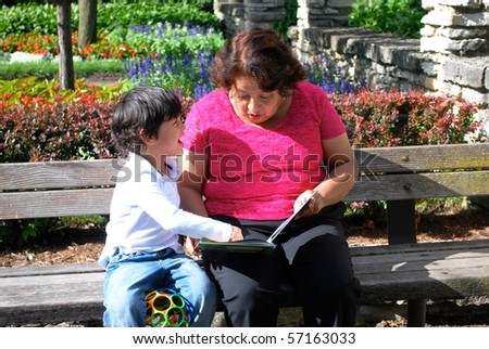 A Hispanic grandmother and grandson reading a book together