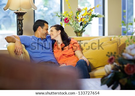 A hispanic man and a caucasian woman in jeans sit on a yellow couch cuddling and smiling at each other in their living room.