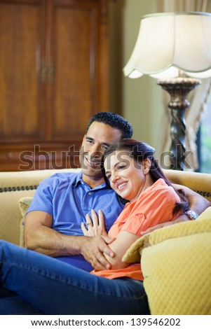 A hispanic man and a caucasian woman in jeans sit on a yellow couch cuddling and smiling in their living room.