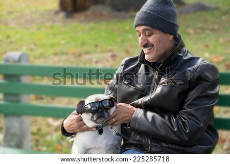 A Hispanic man sitting on a bench with a pug dog, enjoying playing with the dog and putting sunglasses on it.