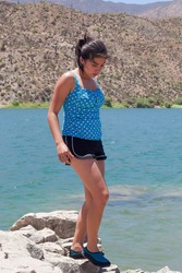 A hispanic teenage girl wearing a blue and white polka dot top walks along a rock wall with a lake and desert landscape in the background.