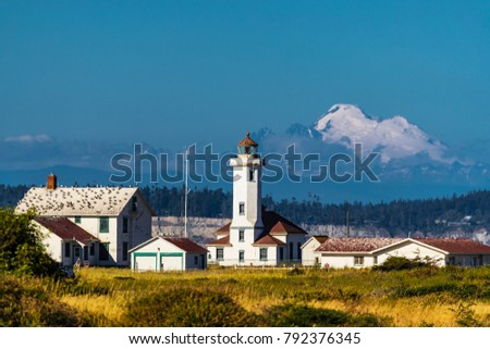 A historic lighthouse on the coast with a huge mountain in the background.  Stockfoto ©
