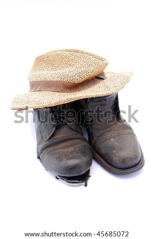 A Hobo's pair of black old broken leather shoes with brown straw hat on top. Image isolated on white studio background.