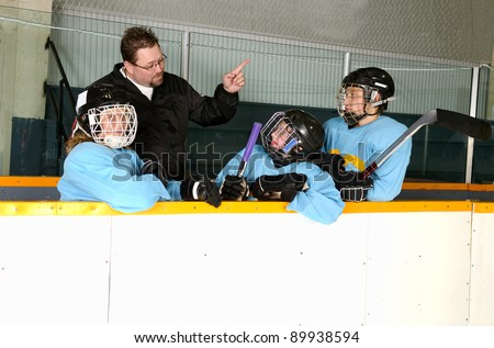 A hockey coach teaches his players from the bench in the arena.