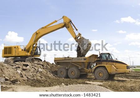 A hoe filling up a dump truck