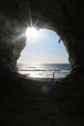 A hole in a cliff or cave at he beach, it is looking like a window or frame, through the hole you can see the blue ocean with some white waves also the sun shine on the horizon