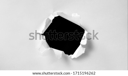 A hole in white paper with torn edges and a black isolated background inside, Ripped black and white paper, copy space Foto stock ©