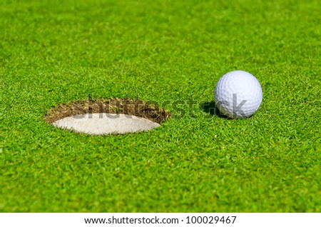 A hole over golf ball on green. Shallow depth of field. Focus on the ball and the hole.