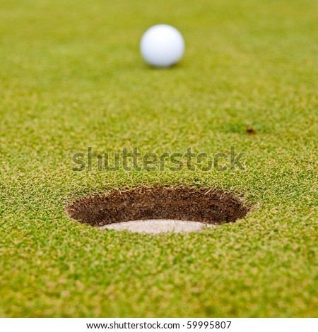 A hole over golf ball on green. Shallow depth of field. Focus on the hole.