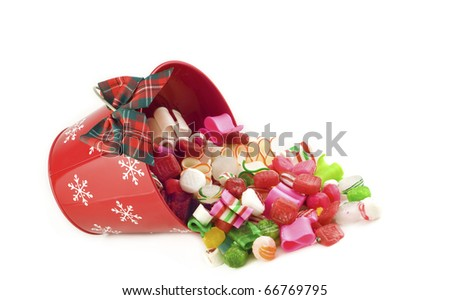 A holiday red bucket full of hard Christmas candy spilling out, isolated on white background