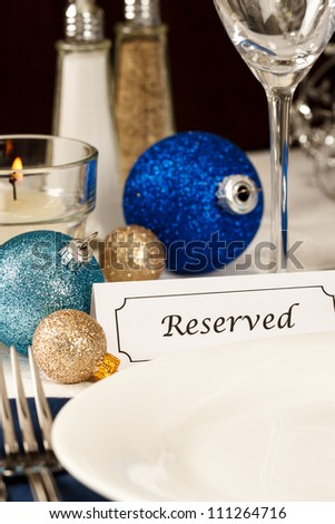 A holiday table setting with an empty plate providing copy space is decorated with blue and gold ornaments and a placard showing a reserved place